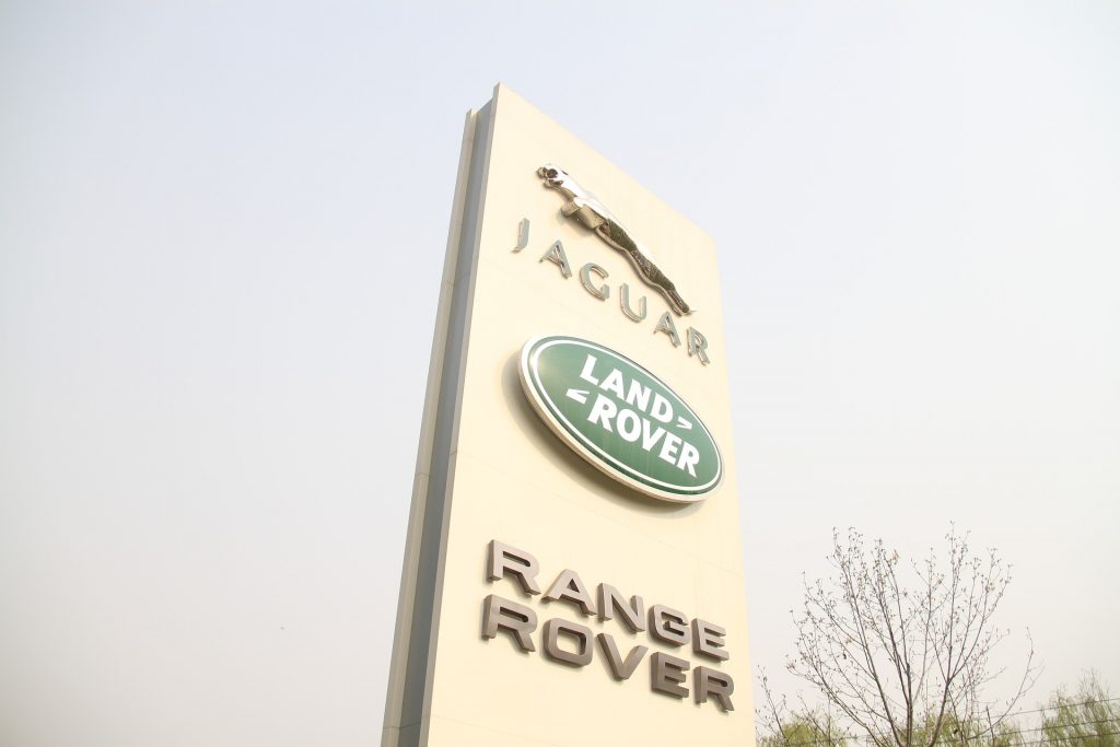 Sign with Jaguar, Land Rover, and Range Rover logo on it